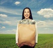 拿着与金钱的成功的妇女袋子 免版税图库摄影