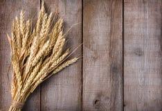 捆在木桌上的麦子耳朵 免版税库存照片