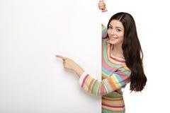 年轻人指向一个空白的委员会的微笑妇女 库存图片