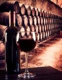 红葡萄酒玻璃近的瓶在老葡萄酒库背景中 免版税库存图片
