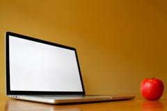 空白的膝上型计算机用在木桌上的苹果 免版税库存照片