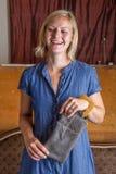 有灰色皮革传动器的笑的白肤金发的妇女 免版税库存图片