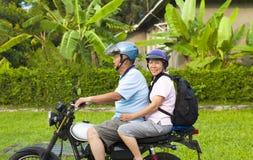 驾驶摩托车的亚洲资深夫妇到旅行 免版税库存图片