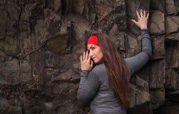 红色头饰带的美丽的少妇在岩石 免版税库存图片
