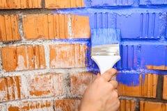 有蓝色的人的手上色了刷子绘画砖墙 库存图片