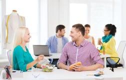 微笑的时装设计师吃午餐在办公室 免版税库存图片