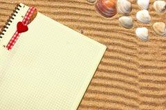 在沙子的黄色方格的笔记薄 库存照片
