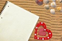 在沙子的白色方格的笔记薄 库存照片