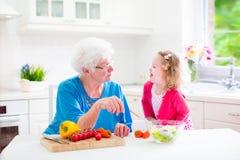 做沙拉的祖母和小女孩 库存照片