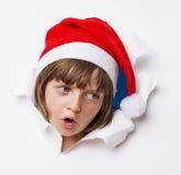 有看在纸的一个孔外面的圣诞老人盖帽的女孩 免版税库存照片