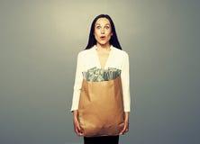 拿着与金钱的惊奇妇女纸袋 免版税库存图片