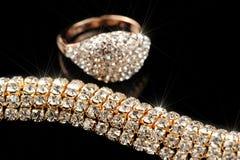 发光的金戒指和项链在黑背景 免版税库存图片
