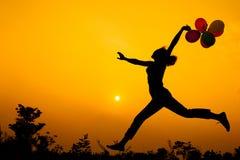 Женщина при воздушные шары скача на природу Стоковая Фотография