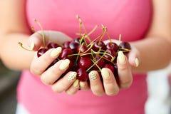 拿着新鲜的樱桃的妇女 库存照片