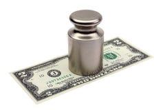 下美元压 与金钱的重量在它下 背景查出的白色 免版税库存照片