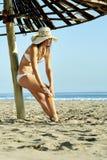 应用遮光剂化妆水的年轻美丽的女孩在伞下在海滩 免版税库存照片