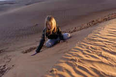 Девушка сидя на дюнах пустыни Стоковые Изображения