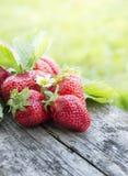 与花和叶子的草莓在老木桌上 库存图片
