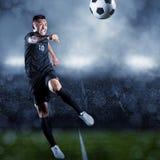 踢球的足球运动员在一个大体育场内 库存图片
