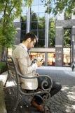 坐在公园的商人 免版税库存图片