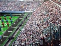制表橄榄球玩具和足球在一个真正的体育场里面 免版税库存照片
