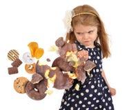 Ребенок пробивая нездоровых змеек высококалорийной вредной пищи на белизне Стоковые Изображения