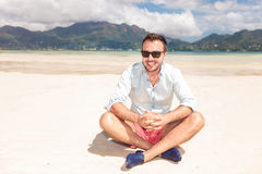 有太阳镜的微笑的年轻人坐海滩 库存照片