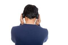 亚裔人与听到与耳机的音乐 免版税库存图片
