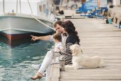 Ευτυχής οικογένεια με τα σκυλιά στην αποβάθρα το καλοκαίρι Στοκ εικόνες με δικαίωμα ελεύθερης χρήσης