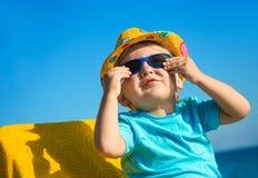 在太阳镜和帽子的男孩孩子在海滩 免版税库存照片