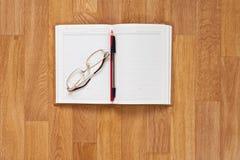 与办公用品的空白的笔记薄在木桌上 库存图片