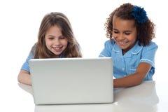 有膝上型计算机的逗人喜爱的矮小的学校女孩 免版税库存照片