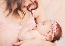 举行充满爱她小的逗人喜爱的睡觉婴孩美国兵的有同情心的母亲 免版税图库摄影