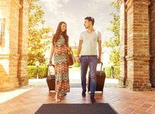 站立在旅馆走廊的年轻夫妇在到来时,寻找室,拿着手提箱 免版税库存照片