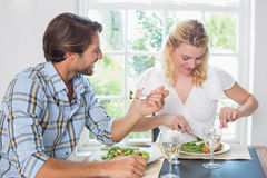 有逗人喜爱的微笑的夫妇膳食一起 免版税库存图片