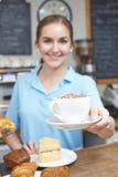 Официантка в клиенте сервировки кафа с кофе Стоковые Фотографии RF