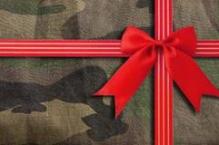 与红色丝带的伪装军事纹理 库存图片
