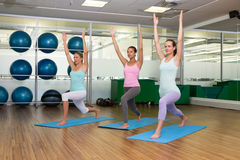在战士姿势的瑜伽类在健身演播室 库存图片