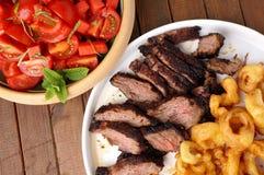 与油炸物洋葱圈和沙拉的牛后腹肉排 图库摄影