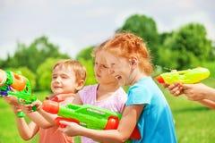 Αστεία παιδιά που παίζουν με τα πυροβόλα όπλα νερού Στοκ εικόνα με δικαίωμα ελεύθερης χρήσης
