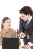 愉快的一起研究计算机的上司和微笑的秘书 免版税图库摄影