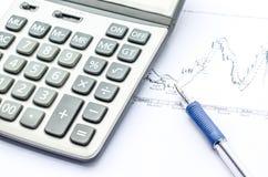 Пер помещенное над финансовохозяйственными статистик и диаграммами Стоковое фото RF