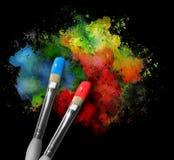 有油漆泼溅物的油漆刷在黑色 免版税库存照片