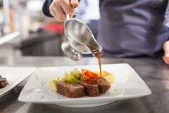 Шеф-повар покрывая вверх по еде в ресторане Стоковая Фотография
