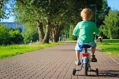小男孩骑马自行车在公园 免版税库存图片