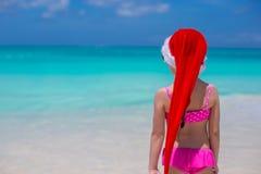 后面观点的红色帽子的圣诞老人逗人喜爱的女孩 免版税库存图片