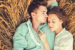 在室外的爱的新夫妇 夫妇拥抱 在停留和亲吻在日落的领域的爱的年轻美好的夫妇 免版税图库摄影