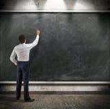 商人提出关于黑板的一个书面报告 免版税库存图片