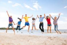 跳跃在海滩的小组朋友 图库摄影