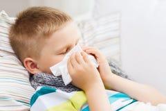 有流感的不适的男孩在家 图库摄影